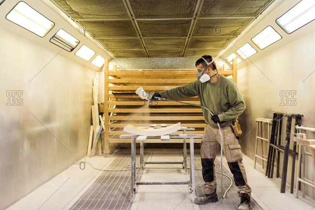 Man woodworking a wooden piece in a spray booth