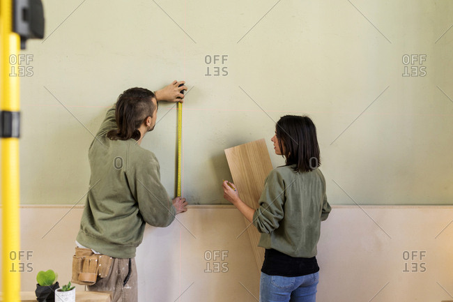 Young man and woman carrying wooden board using laser level