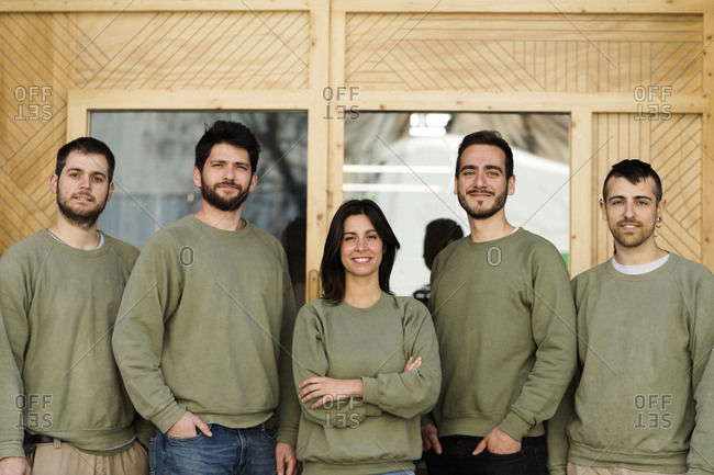 Group of  confident smiling millennials team  in green uniform