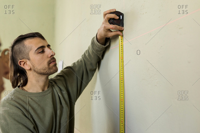 Young man using laser level to measure wall