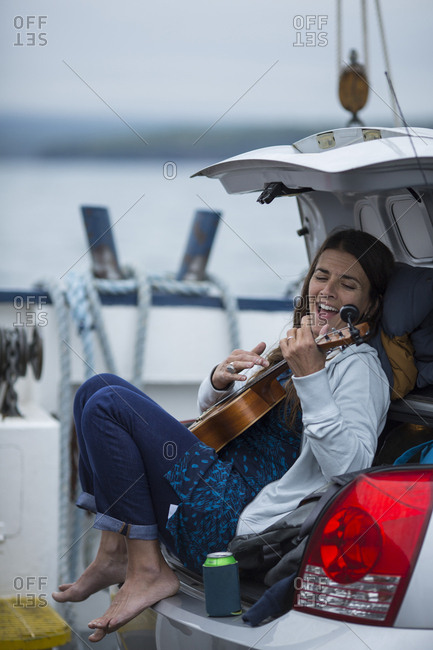 Woman singing and playing ukulele in the open trunk of her car.