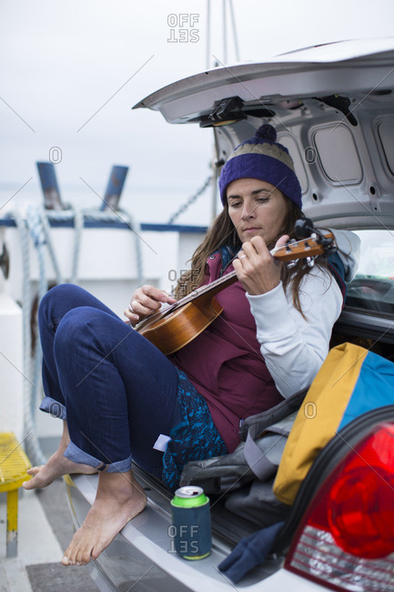 Woman playing ukulele in the trunk of her car on a ferry ride