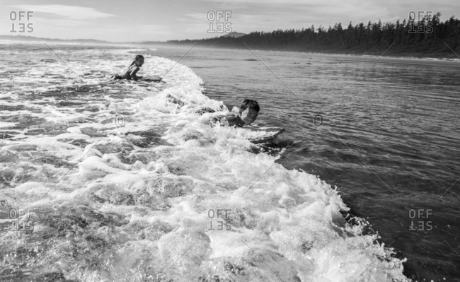 Side view of two children body surfing in ocean waves