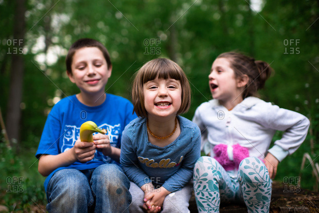 Portrait of three young kids sitting on a log