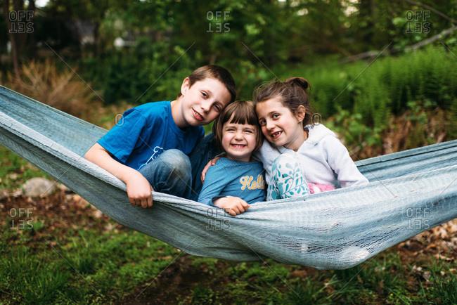 Three young kids cuddling in a hammock