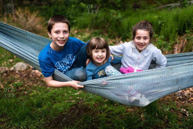 Siblings cuddling in a hammock
