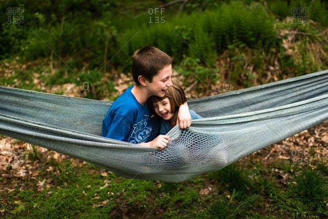 Two siblings cuddling in a hammock