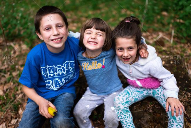 Portrait of three happy kids sitting on a log