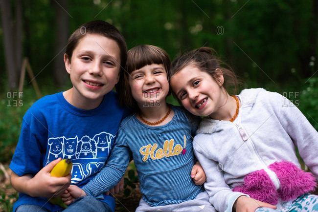 Three happy kids sitting on a log