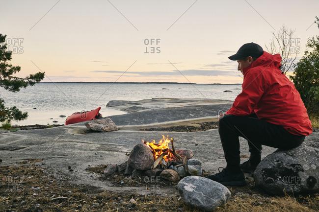 Man having campfire on coast