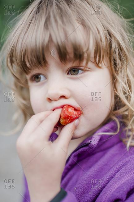 Girl eating strawberry