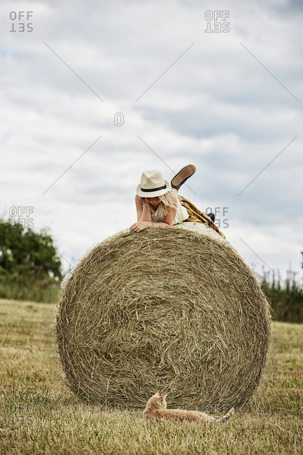 Girl lying on bale of hay