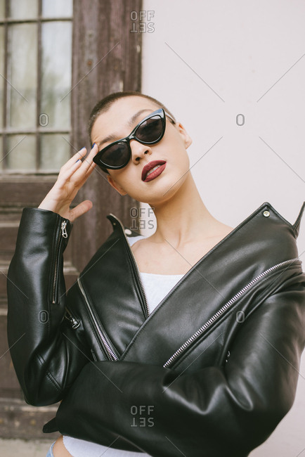 Woman with shaved head wearing sunglasses and a leather jacket