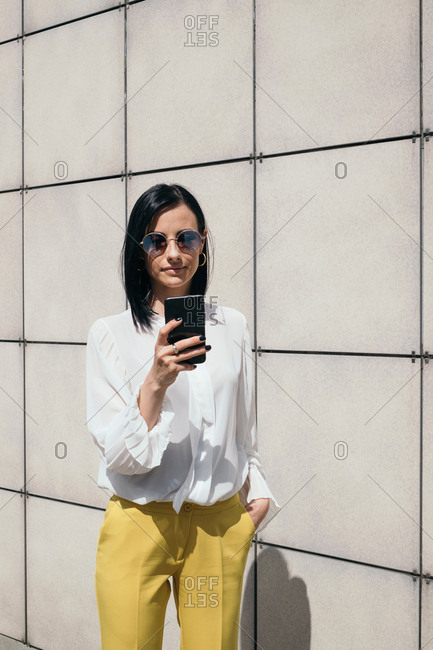 Young businesswoman texting on cell phone outdoors