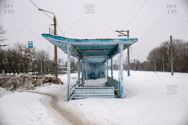 Ukraine - May 17, 2019: Blue bus stop shelter on snowy streetside
