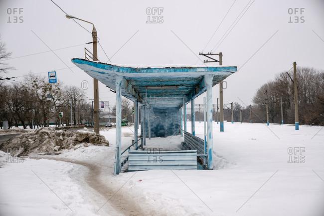 Ukraine - May 17, 2019: Blue bus stop shelter on snowy streetside