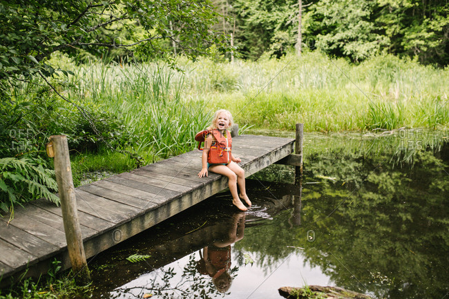Little girl sitting on dock wearing life jacket