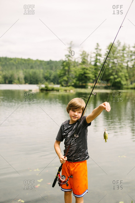 Little boy holding small fish on a lake