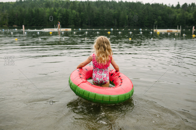 Toddler girl walking into lake with inner tube