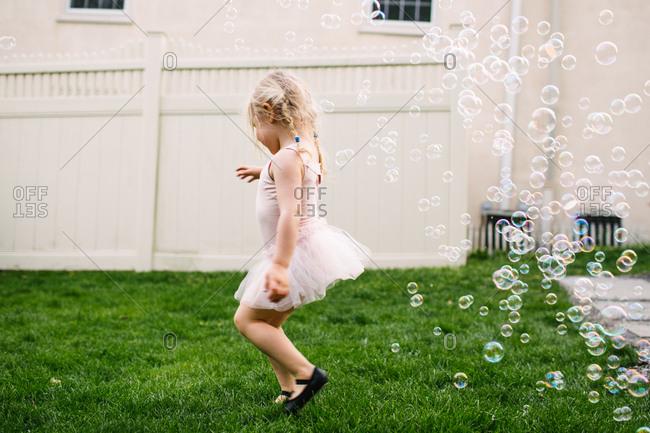 Little girl dancing in ballerina costume with bubbles in backyard