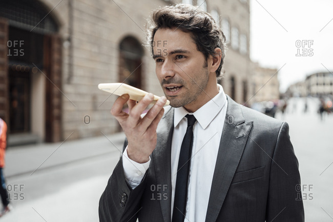 Businessman in the city sending a voice message with the smartphone