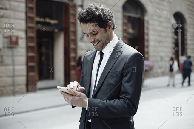 Businessman in the city write on a smartphone
