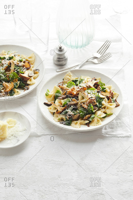 Two bowls of bowtie mushroom and spinach pasta set on a white table next to a plate of grated parmesan cheese.