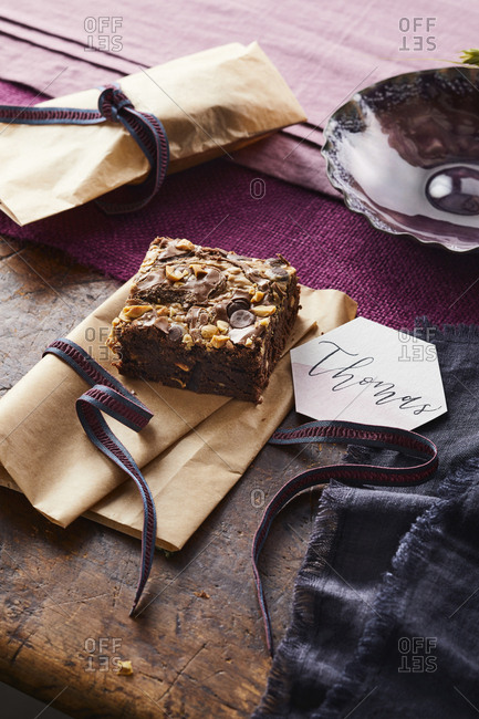 Peanut butter chocolate chip brownie with gift wrapping and ribbons on a wooden table and purple napkin.