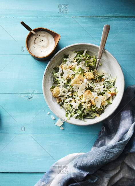 A bowl of brussel sprout caesar salad on a blue wooden table next to a dish of dressing and a napkin.