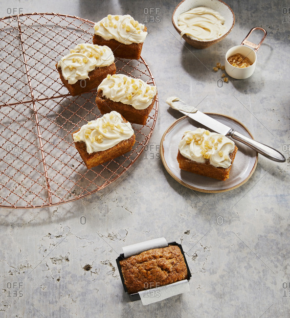 Multiple little frosted carrot cakes  on a plate and tray.