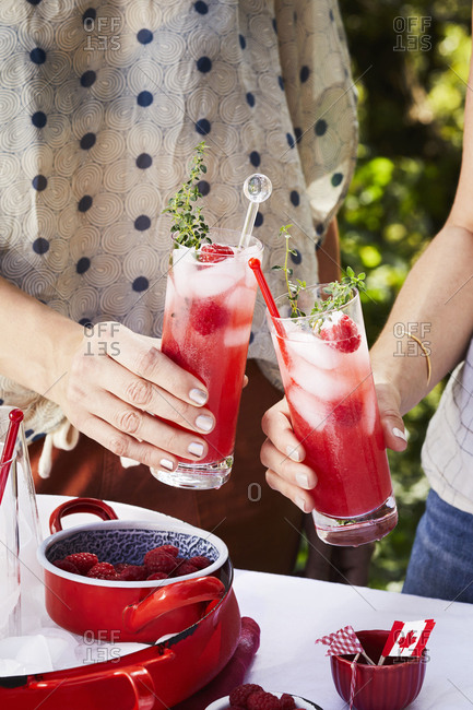 Two friends drinking raspberry cocktails at a summer barbeque