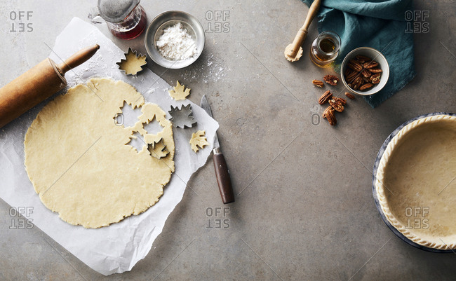 Overhead view of pastry dough with cookie cutters and pecans