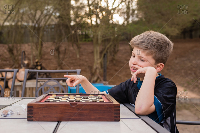 Boy playing checkers outdoors