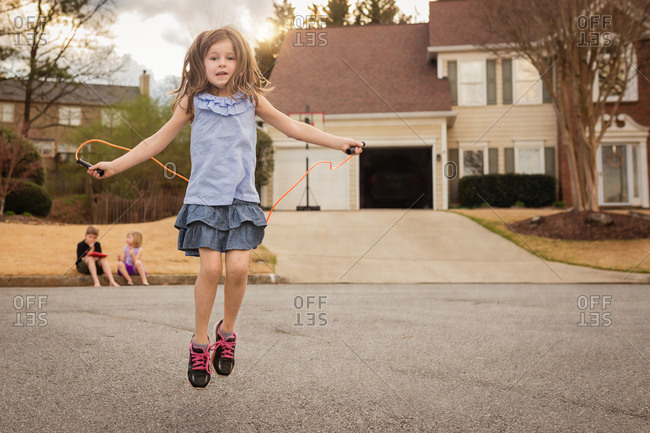Girl jumping rope outside her house