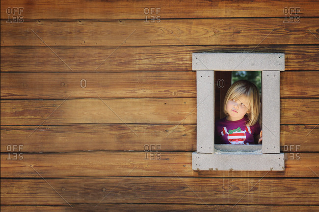 Little girl looking out window in a playhouse