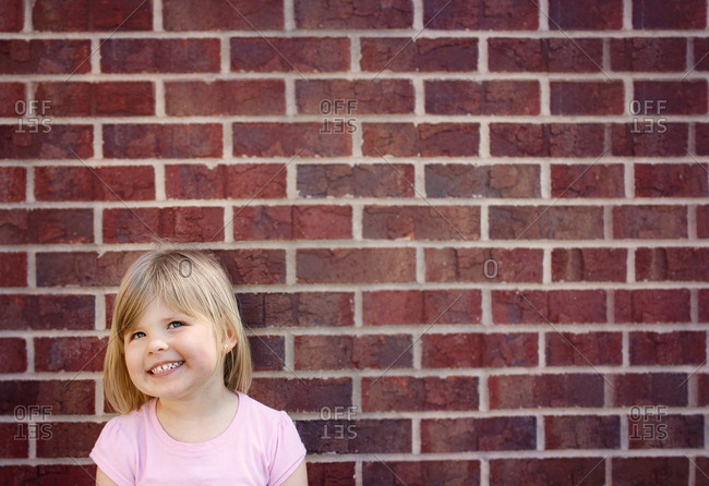Smiling girl standing in front of a brick wall