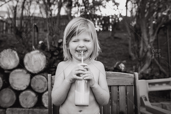 Little girl drinking milk outdoors in black and white