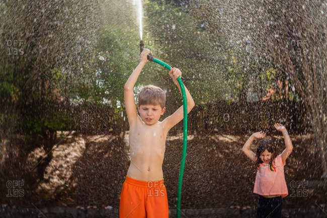 Kids playing with a hose outside