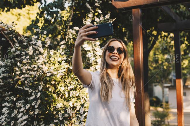 Girl making a selfie with her mobile phone in a park with flowers in the background