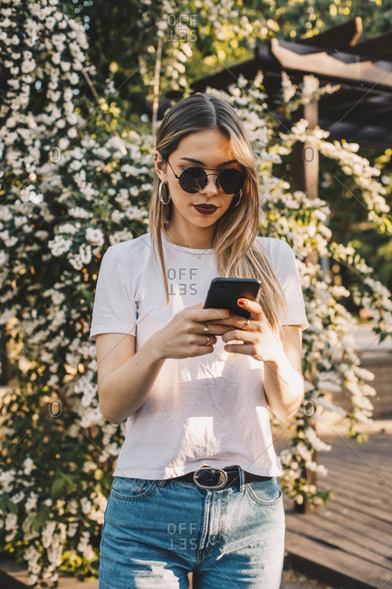 Girl using her mobile phone in a park with flowers in the background