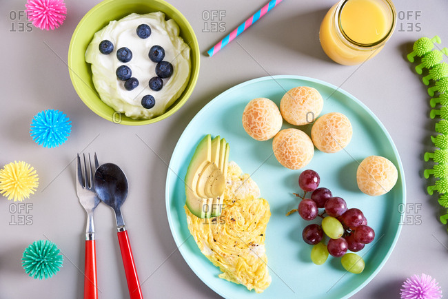 Overhead view of a child's breakfast with toys