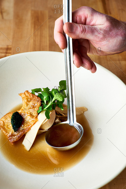 Chef spooning soup into bowl with ladle