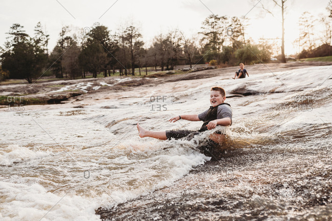 Kids playing in rushing waters of a river