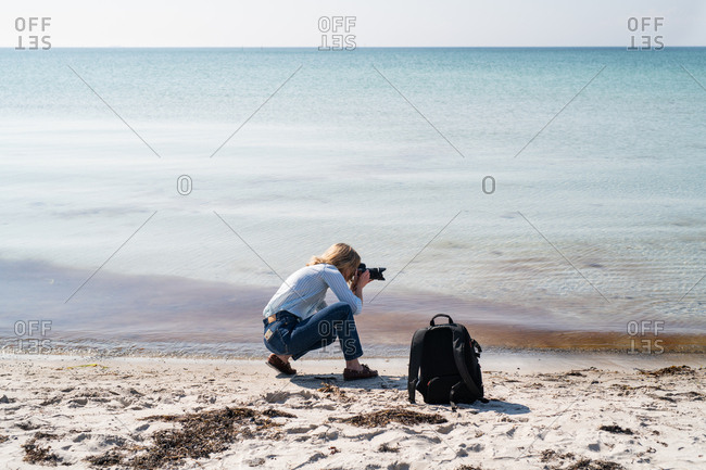 Woman photographing the ocean from a beach