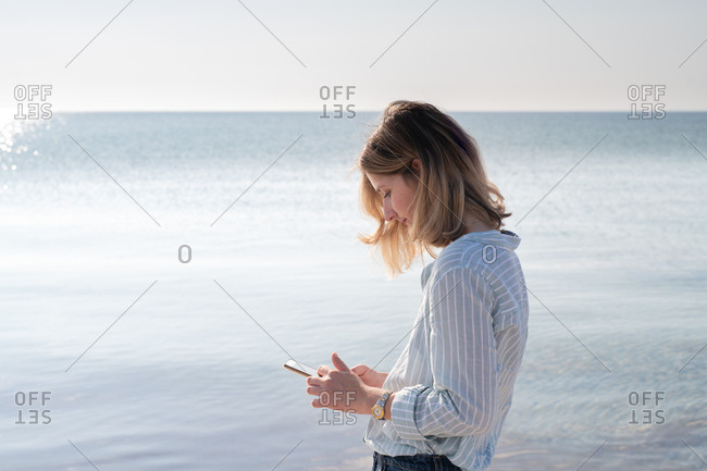 Woman using cell phone a beach
