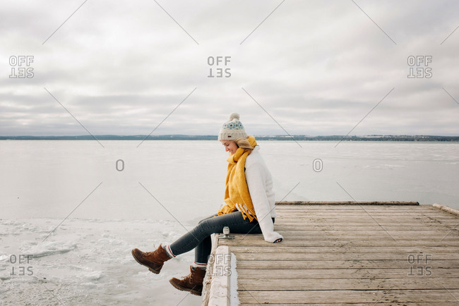 blonde woman sitting on the edge of a pier jetty smiling kicking feet