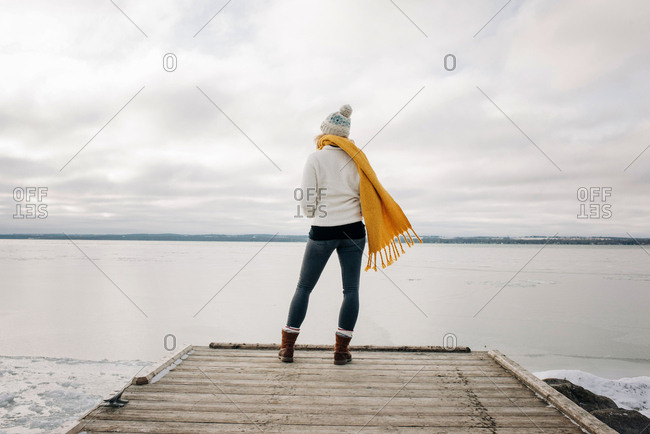 woman standing on the end of a pier jetty looking out to the water