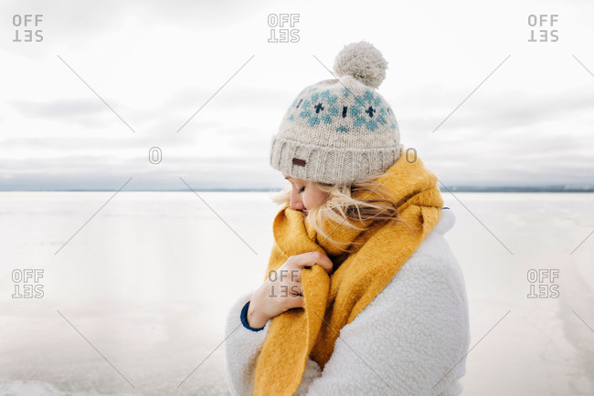 portrait of blonde woman keeping warm at the beach in winter thinking