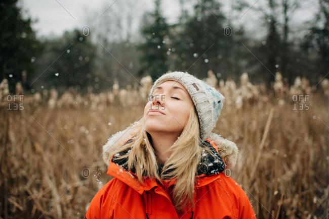 woman standing in the snow with her head up enjoying fresh air outside