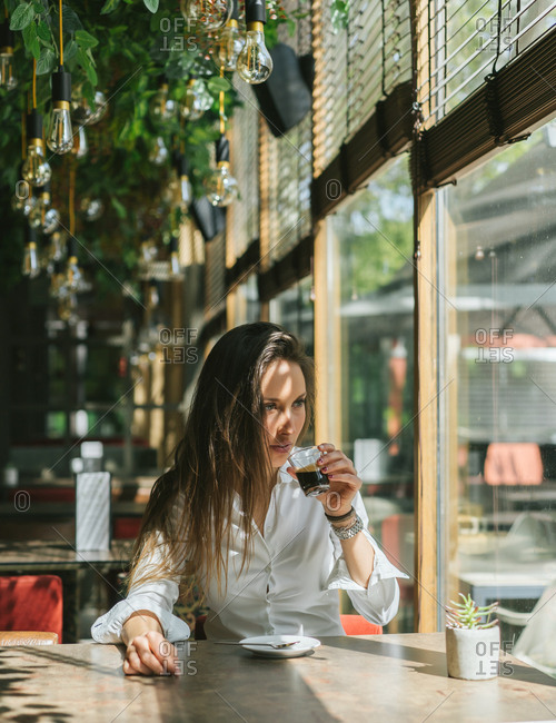 Beautiful Girl Sitting In A Cafe Drinking Espresso